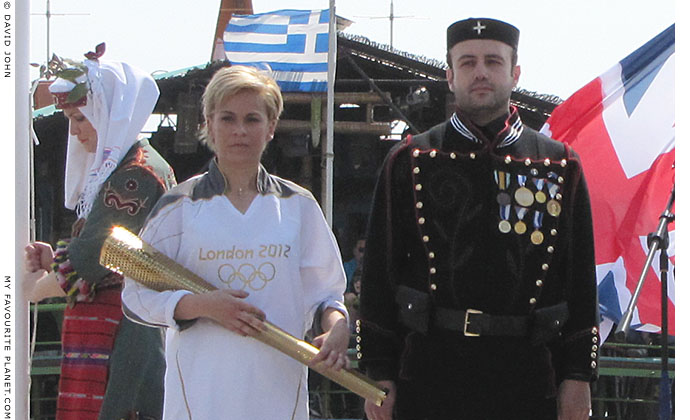 Greek athlete Giota Oikonomou holding her Olympic torch at The Cheshire Cat Blog