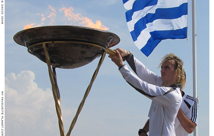 Greek torchbearer Ioannis Melissanidis lights his torch to take the Olympic flame to Kavala, Macedonia, Greece, at The Cheshire Cat Blog