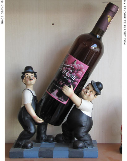Laurel and Hardy carrying a bottle of Turkish wine in a restaurant in Ephesus, Turkey at The Cheshire Cat Blog