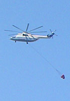 A fire-fighting helicopter flies over Kokkari, Samos, Greece at My Favourite Planet
